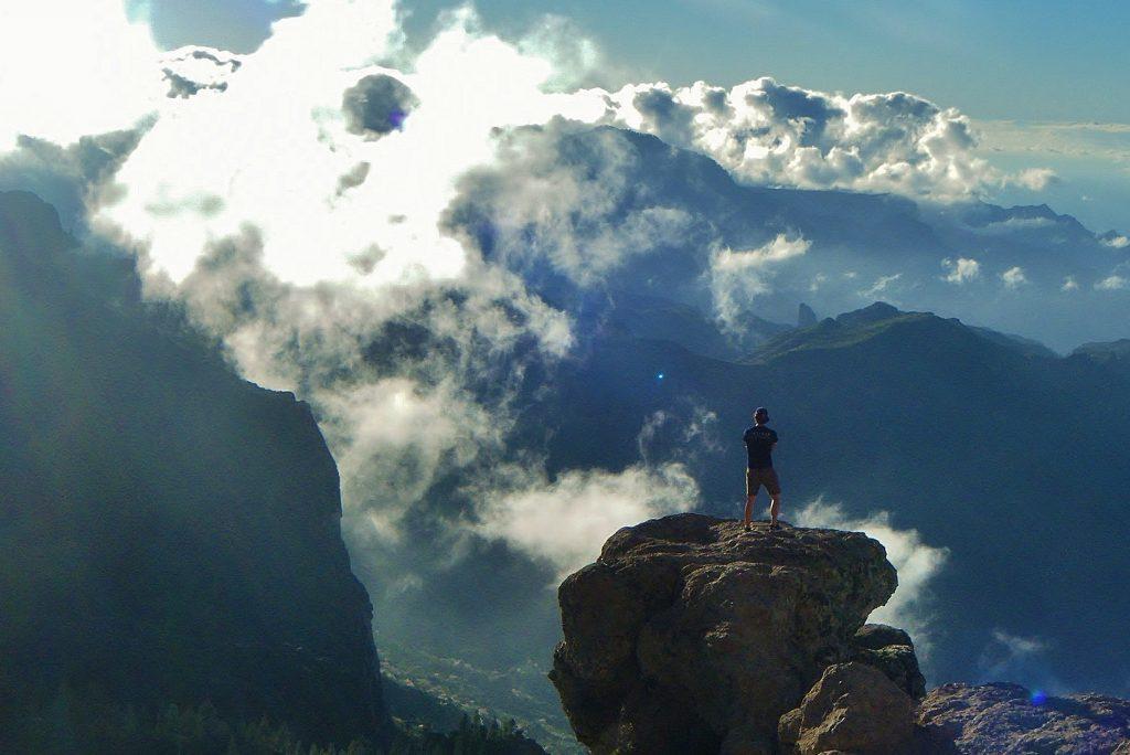 ragazzo a Roque nublo tra le nuvole paesaggio
